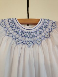 This vintage inspired white imperial batiste toddler girls bishop dress is smocked by hand in blues with blue flowers and green leaves. This dress