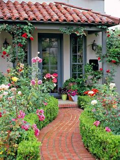 Stone walkways are a characteristic of Mediterranean-style homes and gardens. The curved, red brick walkway leading to this home reflects the roof tiles in both color and pattern. Flowers along the path provide bursts of color.