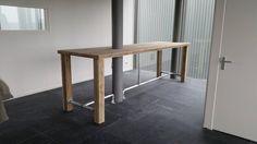 Hoge tafel die op maat gemaakt is voor de ruimte.