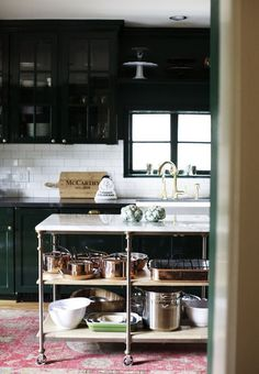 black kitchen (ie painting the cabinets) with existing black counter tops, white or light tiles on wall and interesting color floor tiles