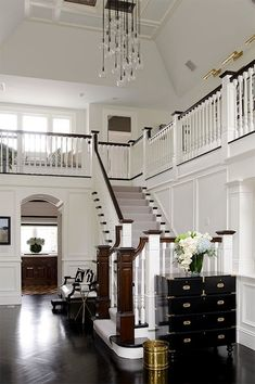 Two story foyer with white wainscotting.Wow! So traditional - but wait - look at the funky chandelier!! Love it!!!