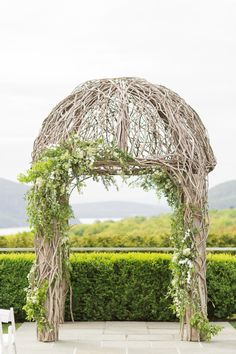 Rustic wedding arch covered in garland: http://www.stylemepretty.com/new-york-weddings/garrison/2016/08/22/neutral-classic-spring-wedding/ Photography: Kelsey Combe - http://kelseycombe.com/#!/HOME