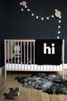 Sark grey walls in nursery with birch crib and black and white Hi blanket