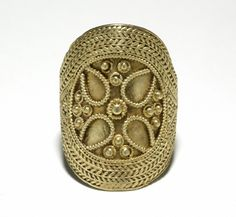 """Ring: ca. 7th century-8th century, middle Anglo-Saxon, gold, """"broad, flat hoop expanding to large oval bezel; covered with bands of twisted wire diverging at the shoulders to enclose a circular design in pearled wire and pellets. Principal motive may be a quatrefoil, pellets in centre and interspaces forming a cross pattee."""""""