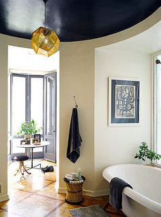 A curved ceiling is made even more dramatic with a coat of glossy black paint, which perfectly contrasts with the black and white furnishings in the bathroom below.