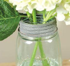 Mason jar flower frog lids help make flower arrangements easy and pretty in a mason jar.