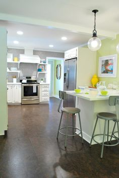 This is an awesome kitchen.  Bright cheery colour, white counters and cupboads, gorgeous lighting, silver appliances, dark floors.