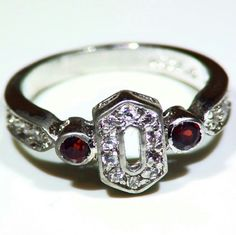 Size 7.5 Gorgeous .925 Sterling Silver woman Ring .925 Sterling Silver stamped. Clear CZ and garnet gemstone. Gorgeous woman's Ring Shipped with a ring box. Good condition. Jewelry Rings