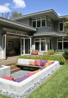 While I don't love the pillows at this outdoor seating area, I do love this backyard in general. I love how many huge windows face this backyard, and I love how the living room opens up into this space. This would be great for entertaining. Backyard Seating, Backyard Landscaping, Garden Seating, Landscaping Ideas, Nice Backyard, Patio Ideas, Garden Ideas, Deck Seating, Backyard Layout