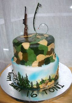 Camo Sweet 16 - Two tier, fondant covered cake.  Bottom has royal icing decor.  Deer, elk and bear.  Top camo.  Sixteen is made with a hunting rifle as the one, and a fly fishing pole as the six. Both made out of gumpaste.