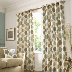Drape these ready made curtains across your window for a modern look full of style, featuring a leaf pattern in soft shades of duck egg blue on a natural background, perfect for a modern interior.