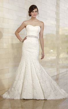 This vintage-inspired wedding dress features a trumpet silhouette in Lace that makes a statement of sophistication. It offers a true sweetheart neckline, a fitted bodice, and a modest court train. Detachable lace illusion jacket and satin sash sold separately. Lace up or zipper back available. $1,000.00 USD
