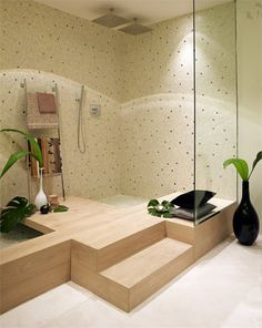 Like the unique shower/tub created in the corner- a very space saving and neat idea. Also like the polka dot style of wall.