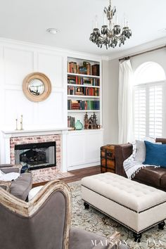 Neutral living room with colorful antique books: Wondering how to seasonally decorate your living spaces without going to too much trouble?  Get my best tips for transitioning from winter whites to neutrals, blues, and greens for a spring living room. #springdecor #springdecorating #springlivingroom #antiquebooks #howtodecorate #seasonaldecor #seasonaldecorating