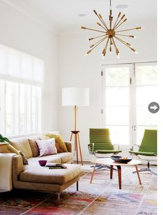 California cool in a mid-century modern living room with tan sofa, sputnik light and green accent chairs