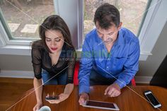 Overhead view of two friends, a man and a woman sitting at the breakfast table working with PC tablet and smart phone drinking morning…