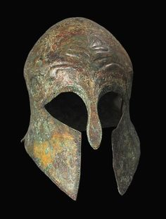 Archaic Greek Bronze Corinthian Helmet, 6th Century BC[[MORE]]The front represents a stylized face with horizontal wide almond-shaped openings for the eyes, divided in the middle by the nose protector and a long slit that separates the paragnathides...