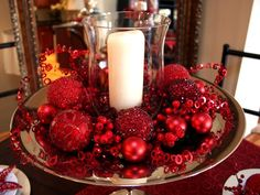Candle display with glass votive, red ornaments, and christmas decor on a tray.