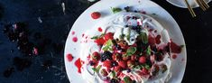 This Pavlova, the famous meringue-based dessert named after Anna Pavlova's tutu, is topped with berries, fresh mint and whipped cream. Classic Pavlova Recipe, Dessert Names, Anna Pavlova, Eton Mess, Creme Egg, Variety Of Fruits, Fresh Mint, Bon Appetit, Healthy Snacks
