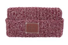 This cuffed beanie is knit out of 100% cotton yarn in burgundy and natural colors and features a brown leather patch...