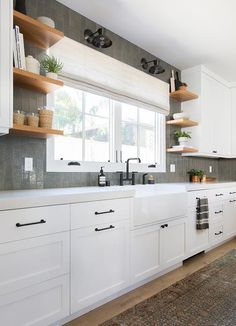 Black industrial light pendants are mounted to vertical gray backsplash tiles above windows dressed in a gray roman shade hung above an apron sink with an oil rubbed bronze deck mount faucet.