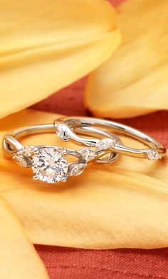 Wispy vines of precious metal entwine toward lustrous marquise diamond buds in this nature-inspired trellis ring. The matched band sits flush and features a trio of marquise diamonds in a delicate floral pattern.