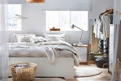 A white IKEA ASKVOLL bed frame in a bright, contemporary bedroom with other bedroom furniture.