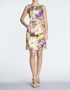 Vestido de sisas y cuello redondo. Lleva pliegues en escote y cintura. Estampado floral en tonos amarillos. Cierre con cremallera dissimulée en lateral.  Lleva forro y cinturón con hebilla personalizada.