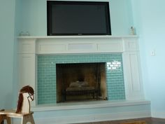 A custom built fireplace surround with glass tile, built-in center channel, and inset for the TV.