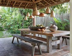 The main cottage's outdoor dining area in Anderson Cooper's Brazil home is furnished with a mix of terra-cotta pendant lights, a custom-made table and a pair of antique farm benches.
