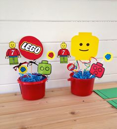 DIY lego party centerpieces. I purchased a printable block party (by Chiquita on Etsy), glued them to wooden craft sticks, stuck them in floral foam and placed them in $1 buckets from Party City. Added shredded paper and bows and ta-da!