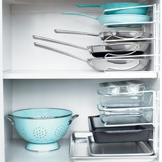 """Stacking pans as opposed to nesting them means you can remove one without having to remove them all. Turn a vertical bakeware organizer on its end and secure it to the cabinet wall with cable clips to prevent toppling. Four-sort dividers, containerstore.com. Top shelf, from bottom: Professional Tri-Ply nonstick frying pan, 10""""; and Professional Tri-Ply frying pans, 10"""" and 8""""; by Martha Stewart Collection, from macys.com."""