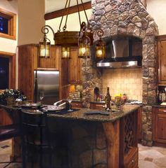 Great mix of stone, wood, and stainless steel.  Love the stone on the bar and range hood.  Kitchen Cabinets/Counters Ultimate Lodge Living