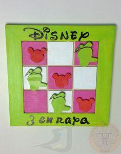 """Juego tradicional de """"Tres en Raya"""", realizado en madera con 4 juegos de fichas para jugar.  Las fichas son la silueta de personajes Disney, Mickey, Goofy, Minnie y Donald. El tablero tiene un tamaño de 20,5 cm x 20,5 cm."""