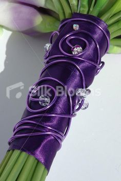 purple ribbon & diamante. I don't know what diamanté is, but you could totally make something like this with your jewelry stuff and be a part of your bouquet!