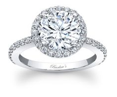Stunning, in vogue, this white gold diamond halo engagement ring will capture the eye of many admirers. Shared prong set diamonds encircle the low profile, large round diamond center and cascade down