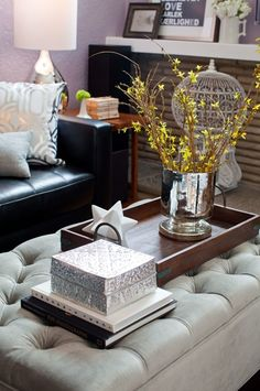 Love so much! Tufted ottomon, silver pattern pillow, hot air balloon cage, mercury glass vessel, pictures on the mantel... great room!