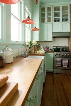 Une très belle cuisine vert menthe où les luminaires, rose corail, apportent un contraste tout en fraîcheur.