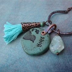 "Starting out with a her own polymer clay pendant, Barbara adds a handforged copper bail, and attaches a handmade tassel, and a piece of aqua vintage crackle glass to one of her own hand forged charm holders.  33"" Long. No clasp, slides easily over head. Finished with a signature copper Second S..."