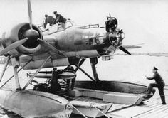Ju-88 loading a torpedo. This is one HUGE bomber .. and it's on pontoons!!!