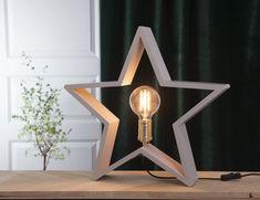 LYSeKIL er en meget dekorativ lampe fra Star Tradingsom er svært anvendelig i sin bruk. Lampen er produsert i treverk, formet som en stjerne og er nå tilgjengelig i mange farger og størrelser. Stjernen kan med fordel plasseres både på bord, gulv og i vinduskarmer. LYSeKIL har en sokkel i messingog den behøveren dekorativ pære for å ta seg best ut. Bookends, Beige, Stars, Lighting, Home Decor, Products, Decoration Home, Room Decor, Sterne