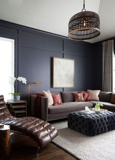 Here's a room that's made with a bit of a mysterious vibe intact. Dark walls highlighted with white windows, tufted pieces accented by a masculine energy, there's a lot of surprise around the room, but it draws us in with its warmth. But because of those tufted elements and minimal accessorizing, it's got a much more formal feeling.