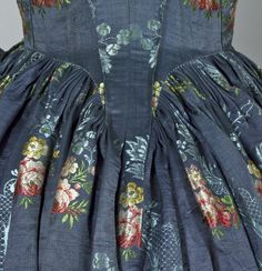 back detail of a Satin brocade open robe and underskirt., 1760 - 1770. Made from dark blue silk satin brocade featuring pale blue meandering foliage and sprays of flowers in pink, yellow and green. The robe has 3/4 length, fitted sleeves and a fitted bodice with a low square neckline at the front and a high square neckline at the back. (c) powerhouse museum