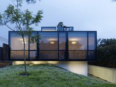 luxurious architectural glass house design on slopy hill with gloomy outdise look and roof top garden and grassy meadow and black frame