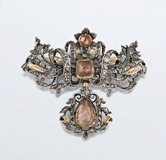 An 18th century topaz and diamond brooch.  The rose-cut diamond openwork looped ribbon bow surmount centrally set with a square and a circular topaz, with reeded gold leaf accents, suspending a matching pear shaped topaz drop, probably Portuguese, in silver mounts, the topaz with coloured foil backs, later brooch fitting.  Sold by Christies.