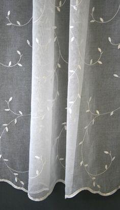 Jednolita, batystowa firanka z delikatnym haftem w kształcie pnących się listków.