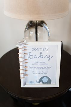 Don't Say Baby is a classic baby shower game. Create a pretty display by printing out a graphic with the description of the game. Place it in a frame, glue ribbon to the edge, and pin mini clothespins along the ribbon. |  Alyssa Renee Photography