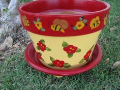 This is an 8 inch terracotta Flower Pot. Pot is painted in yellows and red with bees and flowers all the way around the pot. Saucer is included and is