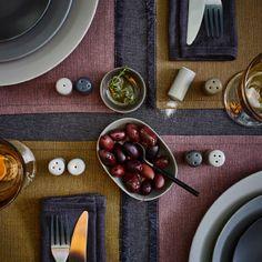 Et dækket bord med små skåle fulde af oliven og salt- og peberbøsser i forskellige grå farver.