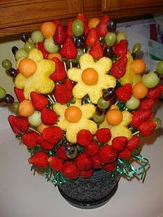 DIY edible arrangement - a sturdy container, Styrofoam block, easter grass,   wooden/bamboo skewers, pineapple, grapes, strawberries, cantaloupe, honey dew, kitchen scissors, flower cookie cutter